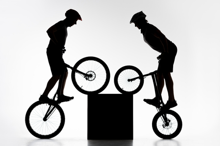 Silhouettes of trial bikers performing stunt with cube synchronously on white background Stock Photo