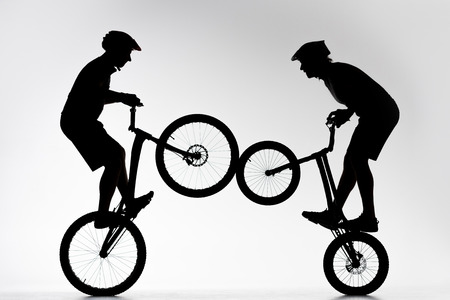 Silhouettes of trial bikers performing stunt synchronously on white background 免版税图像
