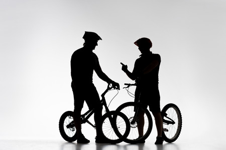 Silhouettes of trial bikers with bicycles chatting on white background