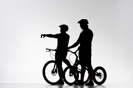 Silhouettes of trial cyclists with bicycles chatting on white background