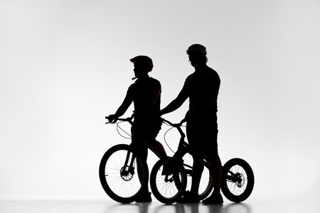 Silhouettes of trial bikers in helmets with bicycles on white background