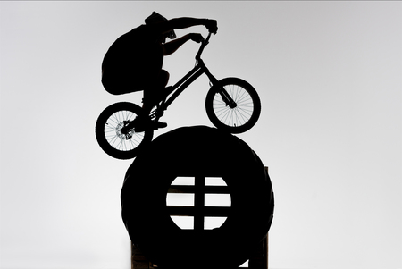 Silhouette of trial cyclist balancing on tractor wheel on white background