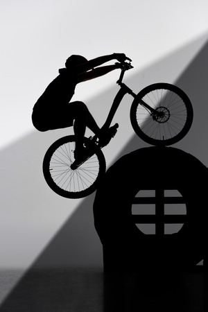 Silhouette of trial biker balancing on tractor wheel on grey background