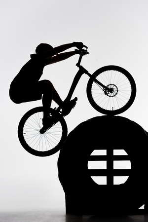 Silhouette of trial biker balancing on tractor wheel on white background