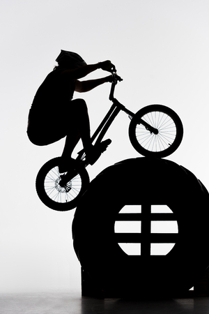 Silhouette of trial biker jumping on tractor wheel on white background