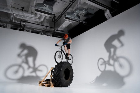 Young athletic trial biker balancing on tractor wheel Stock Photo