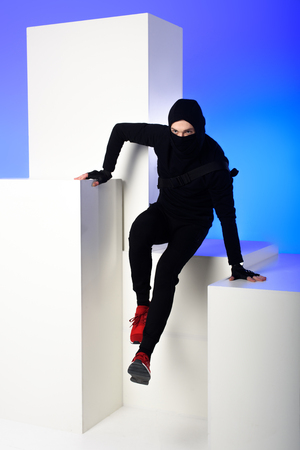 Ninja in black clothing with katana behind getting across on white block isolated on blue background
