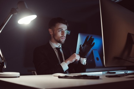 Portrait of hacker wearing gloves while looking at computer screen at table in dark background