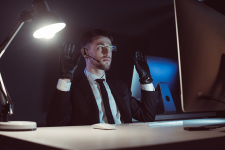 Spy agent in gloves with hands up sitting at table in dark background