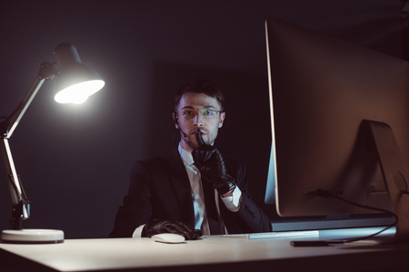 Portrait of spy agent showing silence sign at table with computer screen in dark background Reklamní fotografie