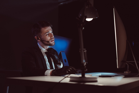 Spy agent in gloves with headset sitting at table in dark background