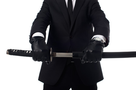Cropped shot of agent in gloves and suit with katana in hands isolated on white background