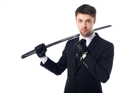 Portrait of spy agent in suit and gloves holding katana isolated on white background