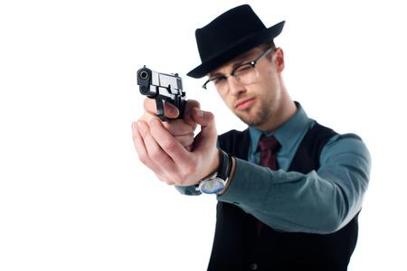 Retrato de agente espía con sombrero y anteojos con pistola aislado sobre fondo blanco. Foto de archivo