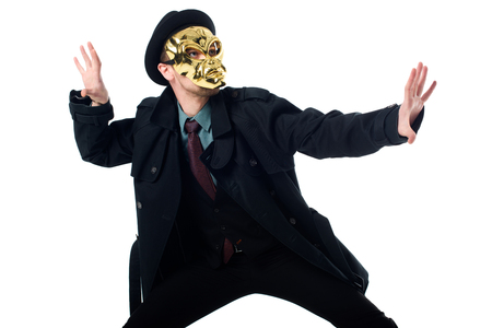 Criminal in mask, hat and black coat posing isolated on white background