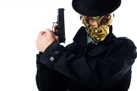 Portrait of criminal in golden mask, hat and black coat with gun in hands looking at camera isolated on white background Stock Photo