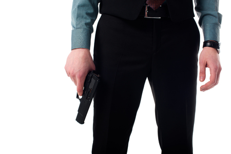Cropped shot of spy agent with gun in hand isolated on white background