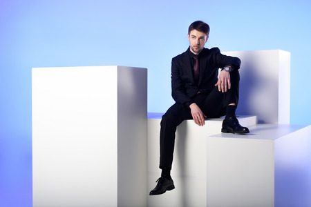 Businessman in black suit sitting on white block isolated on blue background