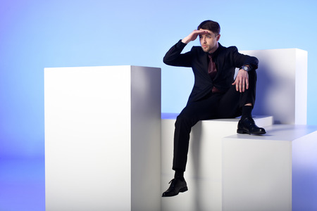 Businessman in black suit sitting on white block and looking away isolated on blue background