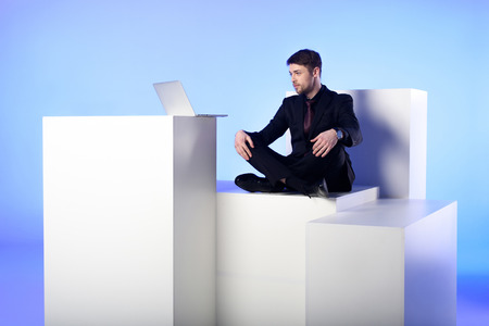 Businessman with laptop sitting on white block isolated on blue background