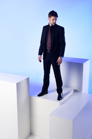 Businessman in black suit standing on white block isolated on blue background
