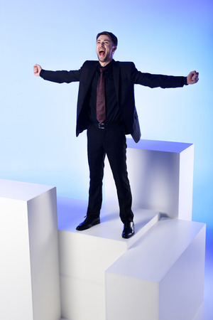 Businessman in black suit with outstretched arms standing on white block isolated on blue background