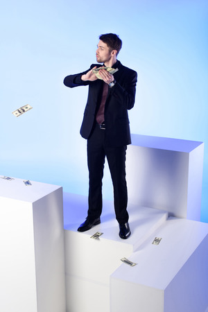 Businessman in suit with dollar banknotes standing on white block isolated on blue background