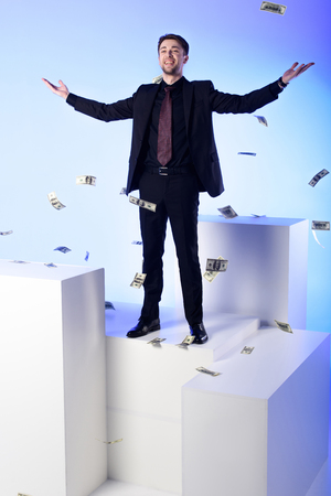 Smiling businessman in suit standing on white block with falling dollar banknotes around isolated on blue background Фото со стока - 110951624
