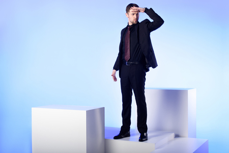 Businessman in black suit standing on white block and looking away isolated on blue background 스톡 콘텐츠