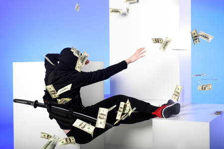 Back view of ninja in black clothing catching dollar banknotes on white blocks isolated on blue background