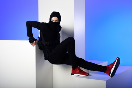 Ninja in black clothing standing on white blocks isolated on blue background 写真素材