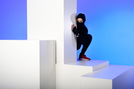 Ninja in black clothing hiding behind white block isolated on blue background 写真素材