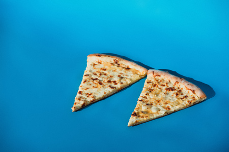 Close up view of pieces of cooked pizza isolated on blue background Stok Fotoğraf