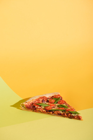 Close up view of piece of pizza with cherry tomatoes and basil on colorful backdrop Stock Photo - 110951879