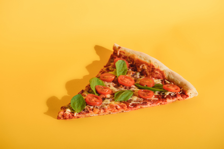 Close up view of piece of pizza with cherry tomatoes and basil on orange backdrop