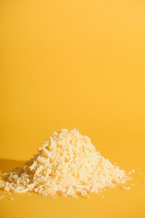 Vista ravvicinata del formaggio grattugiato su sfondo arancione Archivio Fotografico