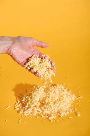 Cropped shot of female hand with grated cheese on yellow backdrop