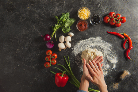 Cropped shot of woman braking dough while cooking Italian pizza on dark tabletop