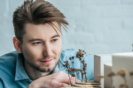 Selective focus of architect looking at self made building model in office Banco de Imagens
