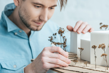 Selective focus of focused architect looking at self made building model in office 版權商用圖片