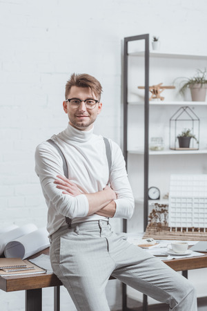 Portrait of smiling architect in eyeglasses with arms crossed leaning on workplace in office