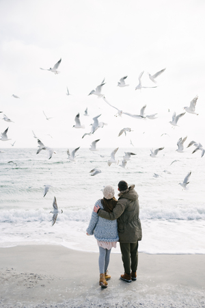 Back view of young couple hugging and looking at seagulls