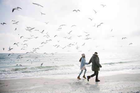 Young couple holding hands and walking on winter sea shore and looking at seagulls