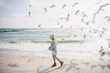 Beautiful stylish girl on winter seashore with seagulls Archivio Fotografico - 110952016