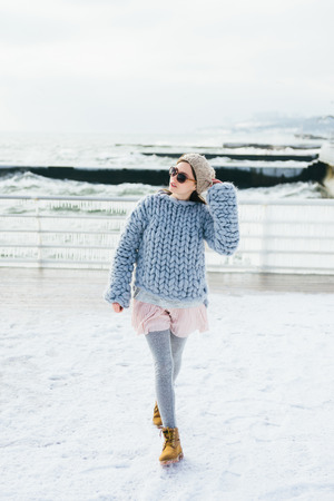 Stylish young girl in sunglasses and light blue merino sweater on winter quay