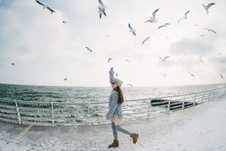 Beautiful young stylish girl on winter quay with seagulls Archivio Fotografico - 110952039