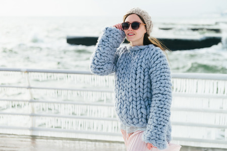 Stylish young girl in sunglasses and merino wool sweater on winter quay Stockfoto
