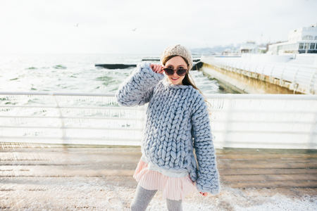 Beautiful girl posing in merino wool sweater and sunglasses on winter quay