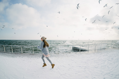 Beautiful young girl running on winter quay with seagulls