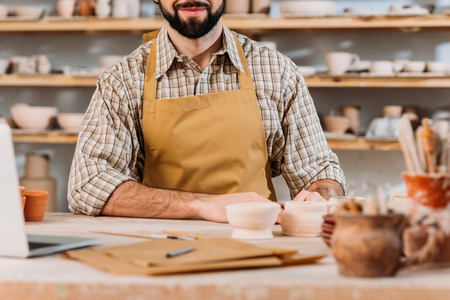 Cropped view of man in apron in pottery workshop Imagens